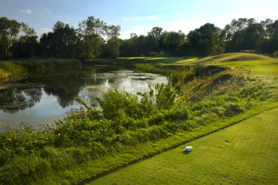 The green of hole 17 on The River Course in the distance with a water hazard on the left.