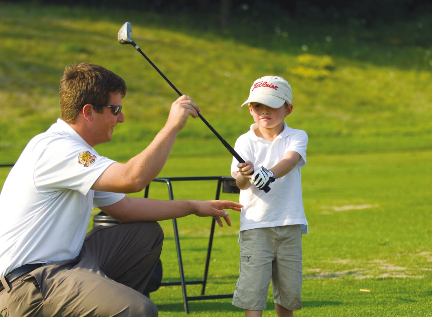 junior golfer receiving golf swing instruction