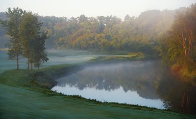 The green of hole 11 on the River Course in the distance with morning fog in fall.