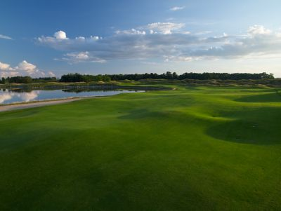 The green of hole 17 on the irish Course at sunrise with water on the left side of the fairway.
