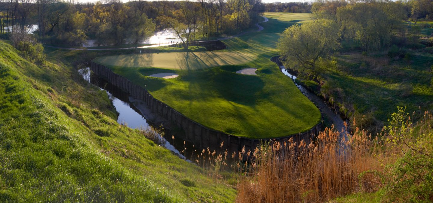 An ariel view of the green of hole 14 on the Meadow Valleys course that shows the water on three sides of the green.
