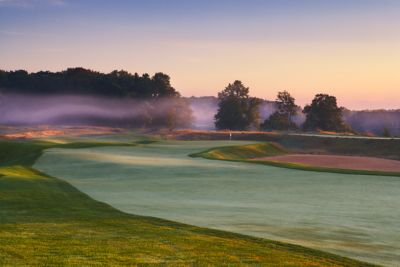 The fairway with the green of Hole 16 of the Meadow Valleys course with morning fog.