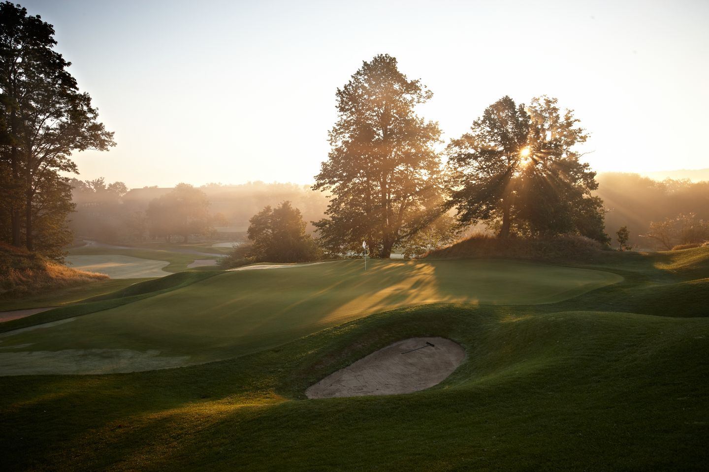 The green of hole 10 on the Meadow Valleys course at sunrise with a bunker on the left.