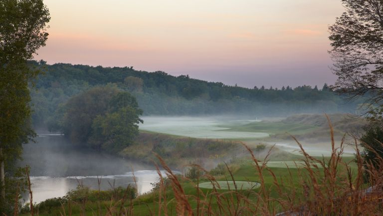 The first hole of the River Course with the green in the distance and a water hazard on the left.