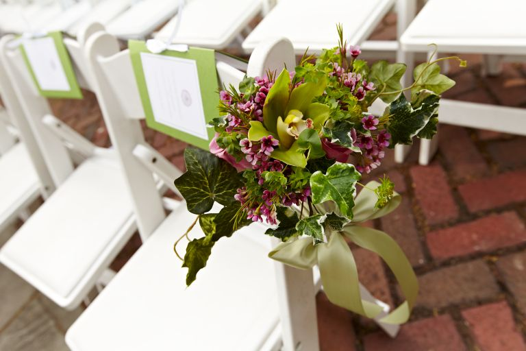 Flowers tied to a chair at a wedding