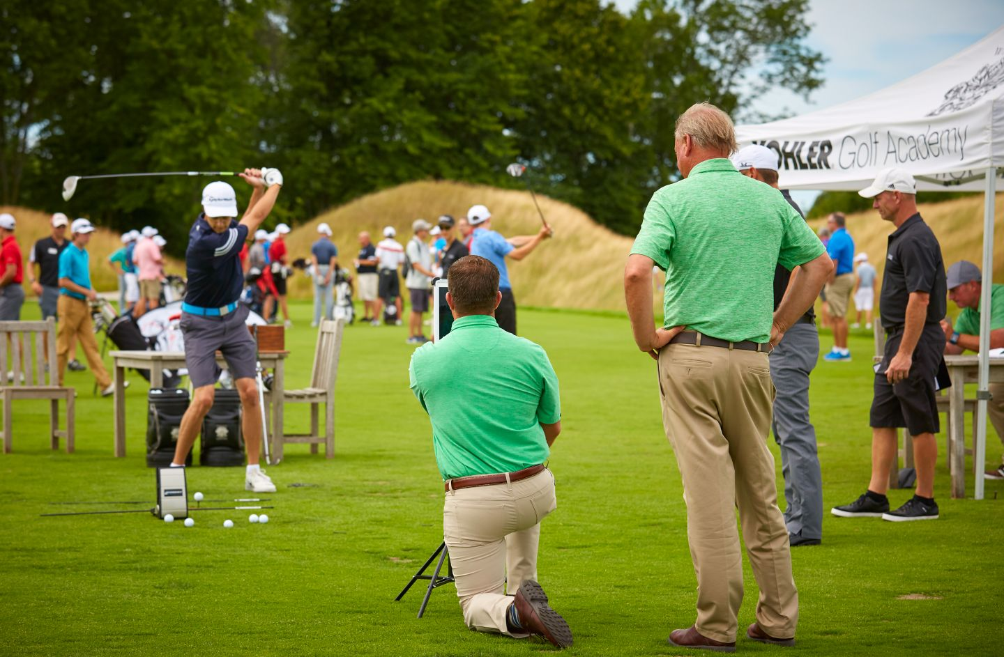 Golfers receiving golf instruction at golf course practice facility