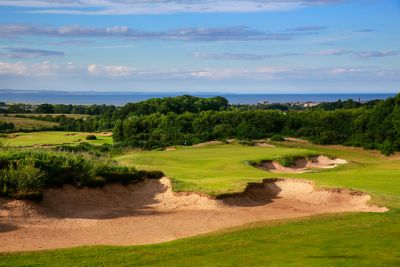 No. 13 Braw View. Looking towards the 13th green at The Duke's over a deep bunker with views of St Andrews in the background.