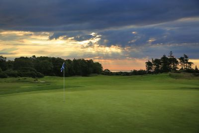 No. 5 Beeches. 5th green at The Duke's golf course with flag in foreground and the sea in the background.
