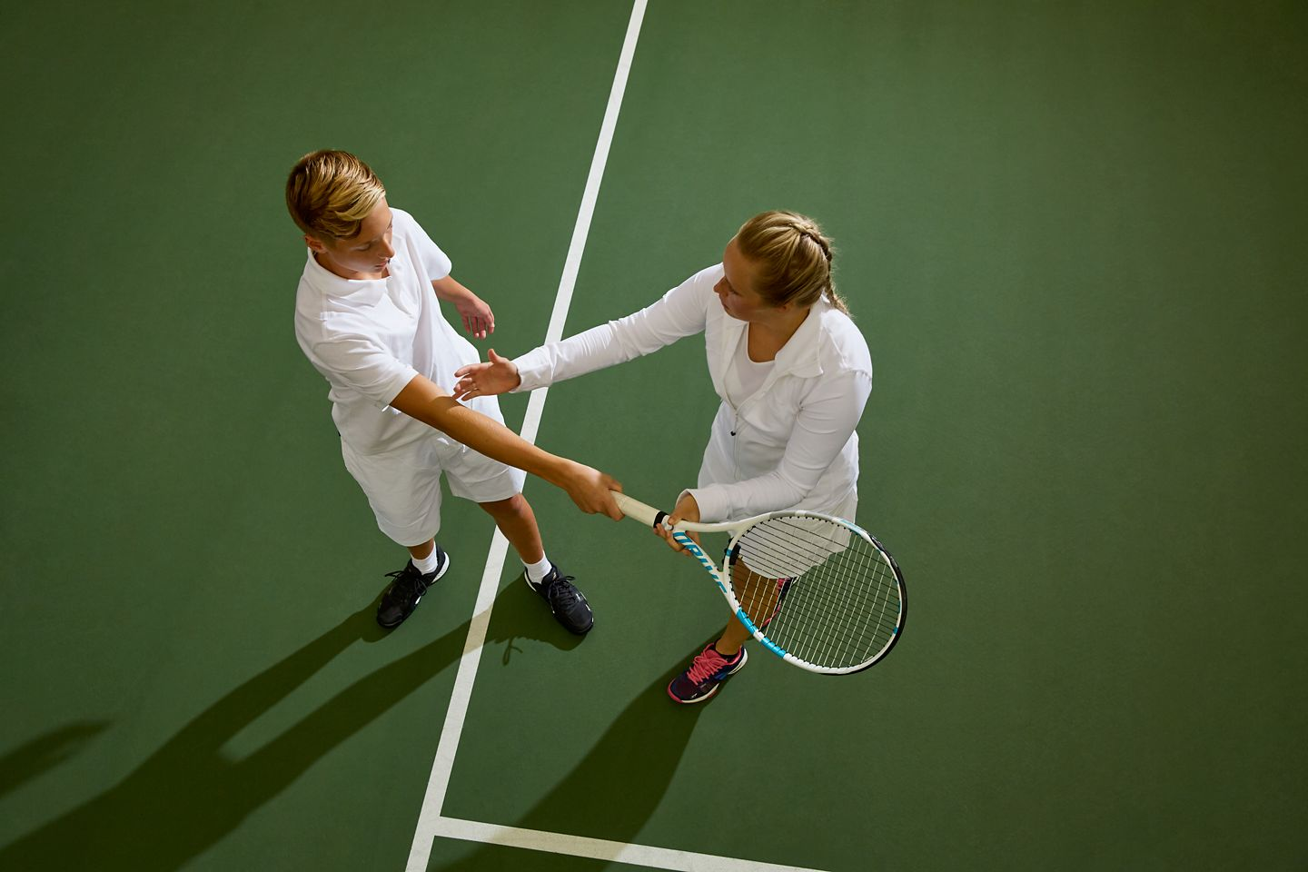 Tennis instructor teaching youth player