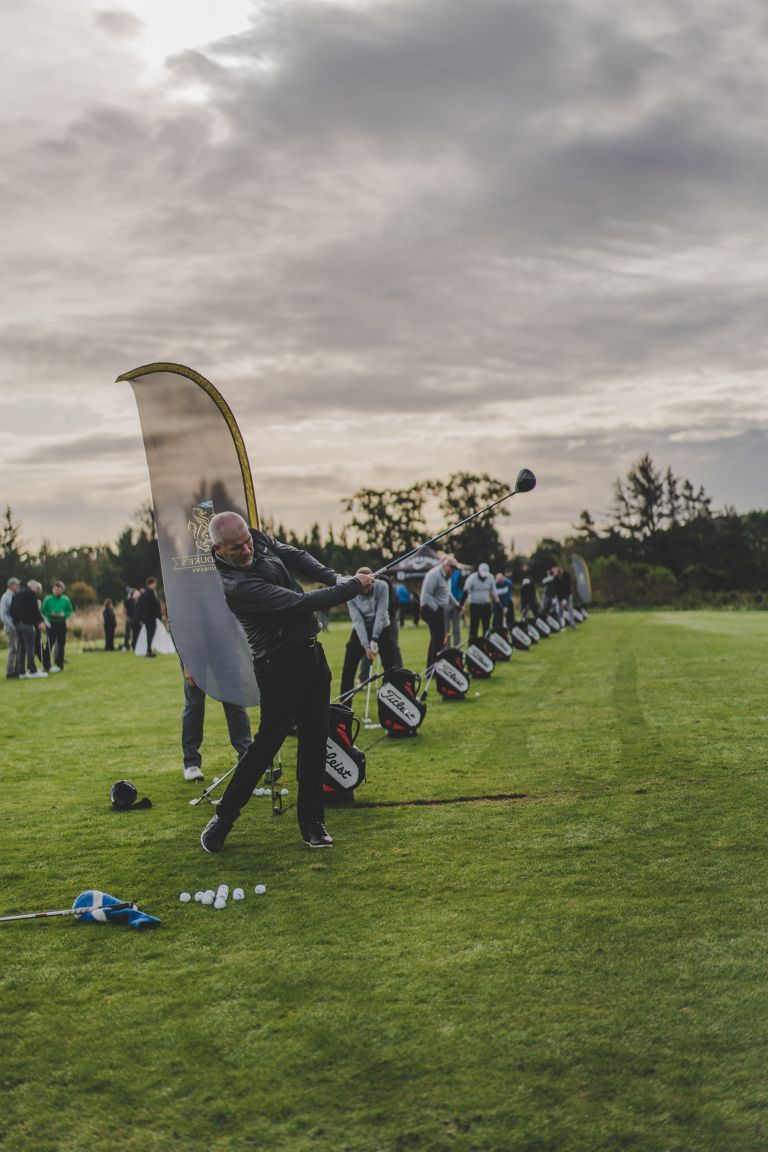 Group practicing on the driving range of The Duke's