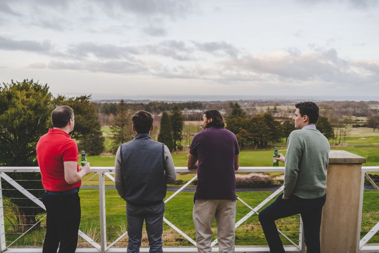 Golfers on The Duke's Clubhouse balcony looking towards St Andrews