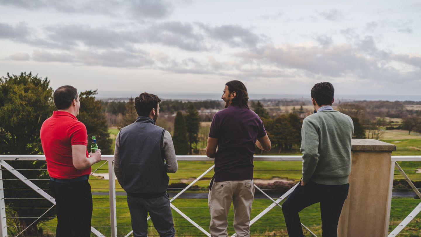 Group of golfers on the clubhouse balcony overlooking the course.