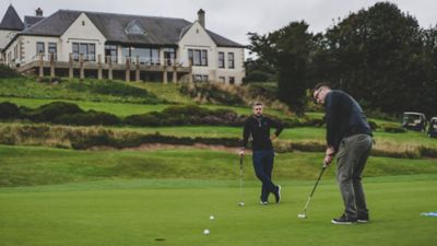 Two men putting on a green on The Duke's golf course, St Andrews
