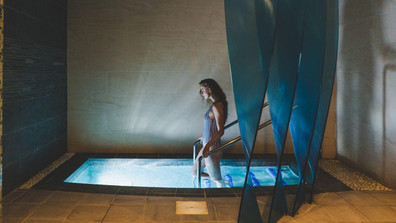 Woman walking into Kohler Waters Spa plunge pool
