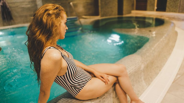 Woman relaxing by Kohler Waters Spa hydrotherapy pool