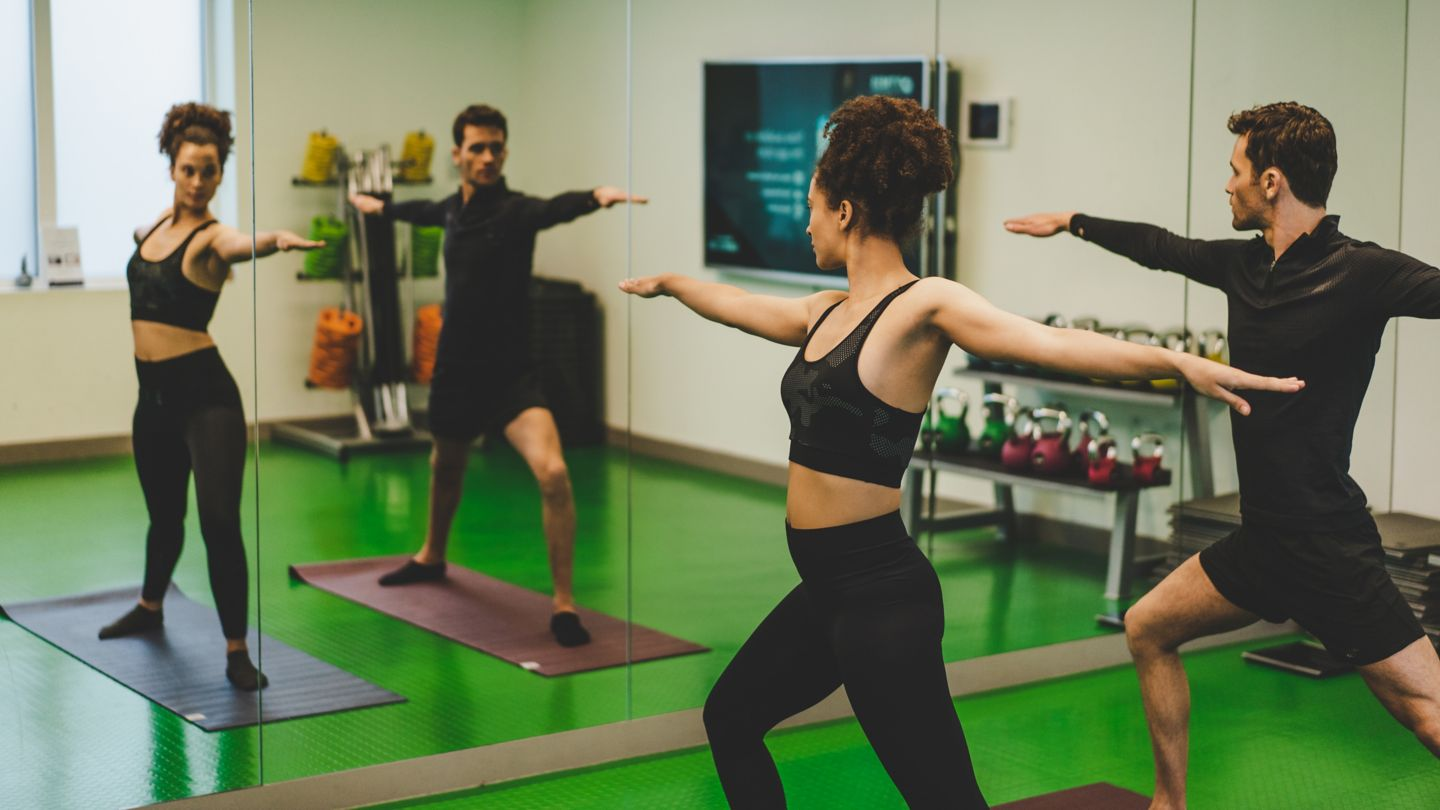 Couple doing yoga in the Kohler Waters Fitness Centre