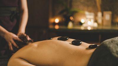 Woman receiving a hot stone massage in Kohler Waters Spa