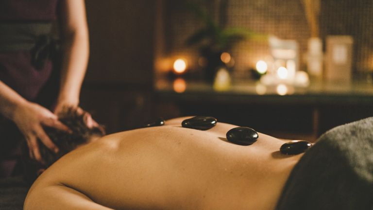 Man receiving hot stone massage at Kohler Waters Spa, St Andrews
