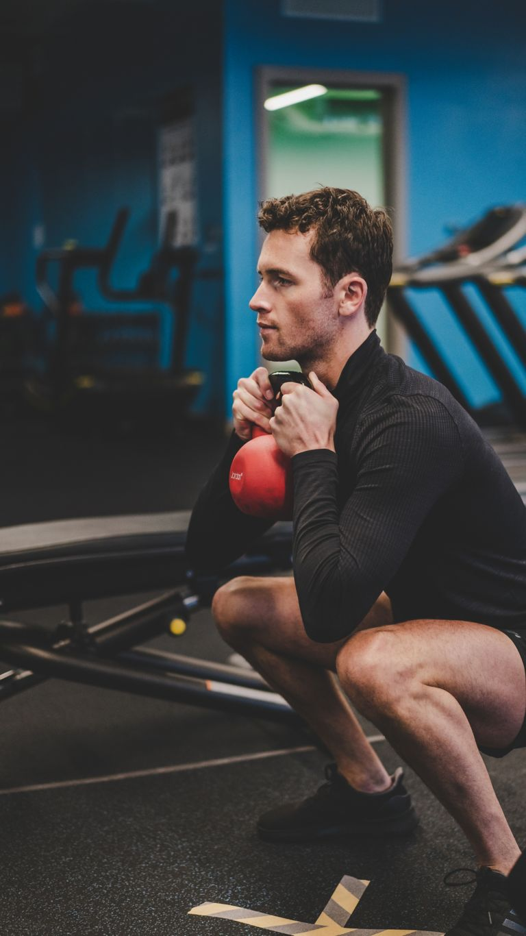 Male working out with a kettlebell in Kohler Waters Spa Fitness Centre.