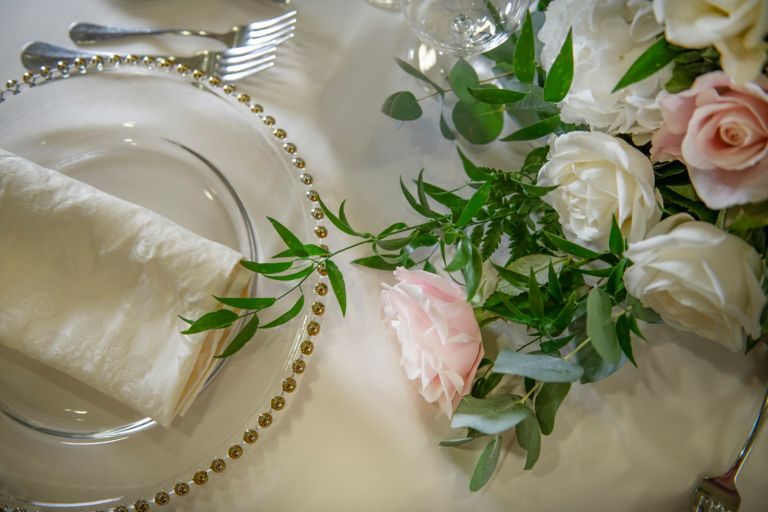 Pink rose next to a charger plate. Weddings at the Old Course Hotel, Golf Resort & Spa