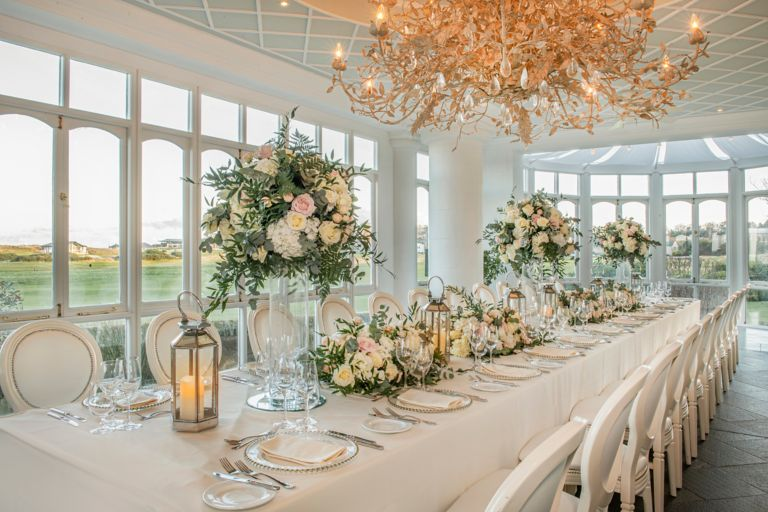 Wedding reception set up with flower arrangements and table set ups in the Conservatory venue space at the Old Course Hotel, Golf Resort & Spa looking out over the world famous golf course.