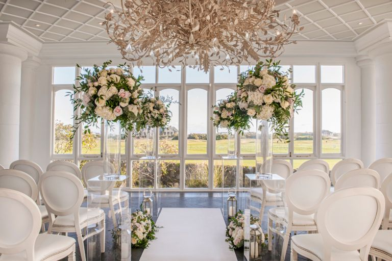 Wedding ceremony set up with flower arrangement in the Conservatory venue space at the Old Course Hotel, Golf Resort & Spa looking out over the world famous golf course.