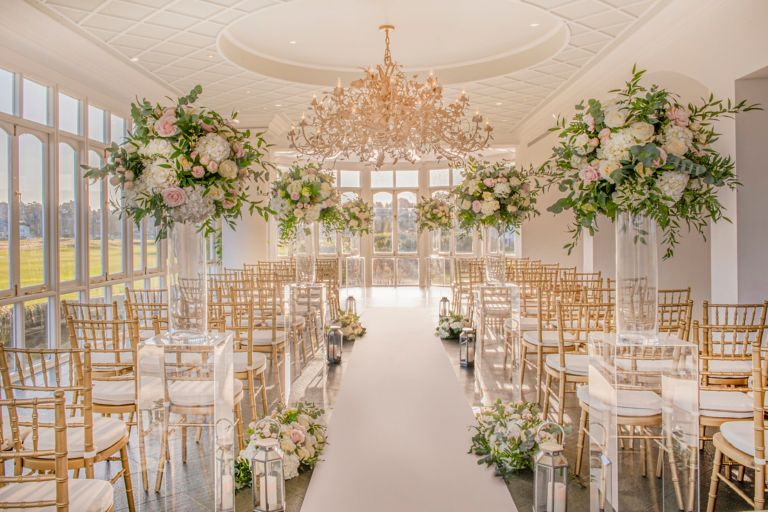 Wedding ceremony set up with flower arrangements and chiavari chairs in the Conservatory venue space at the Old Course Hotel, Golf Resort & Spa looking out over the world famous golf course.