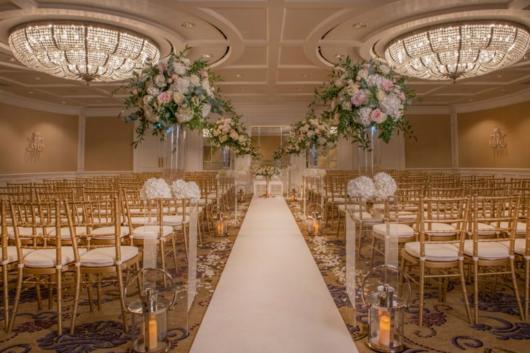 Wedding ceremony set up with flower arrangement and chiavari chairs in the grand Ballroom venue space at the Old Course Hotel, Golf Resort & Spa.
