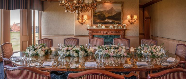 Wedding reception set up with flower arrangement and table set ups in the grand Boardroom venue space at the Old Course Hotel, Golf Resort & Spa with breathtaking views over the world famous golf course.
