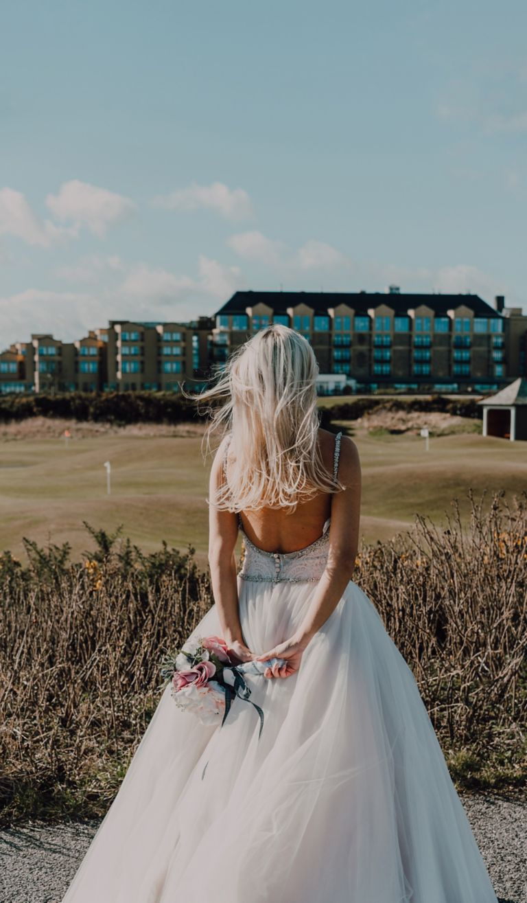 Bride standing on West Sands Beach looking towards the Old Course Hotel, Golf Resort & Spa