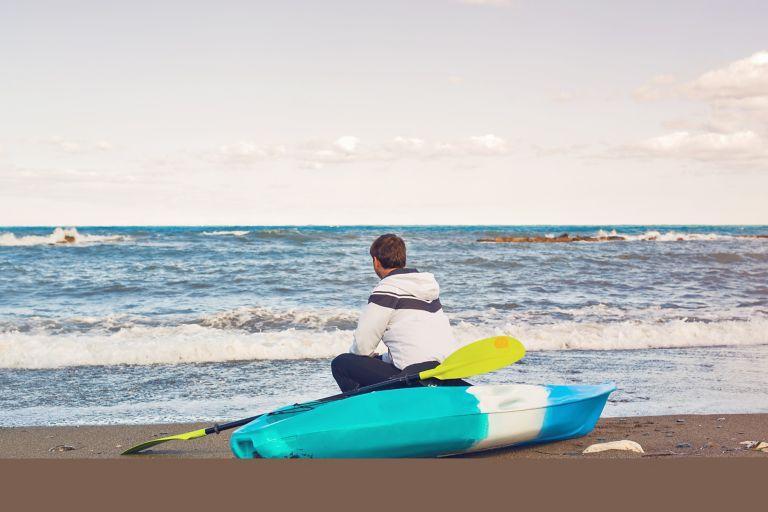 Man sitting on a kayak on the beach