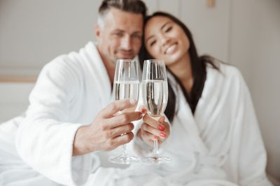 Man and woman enjoying a glass of prosecco in their bathrobes