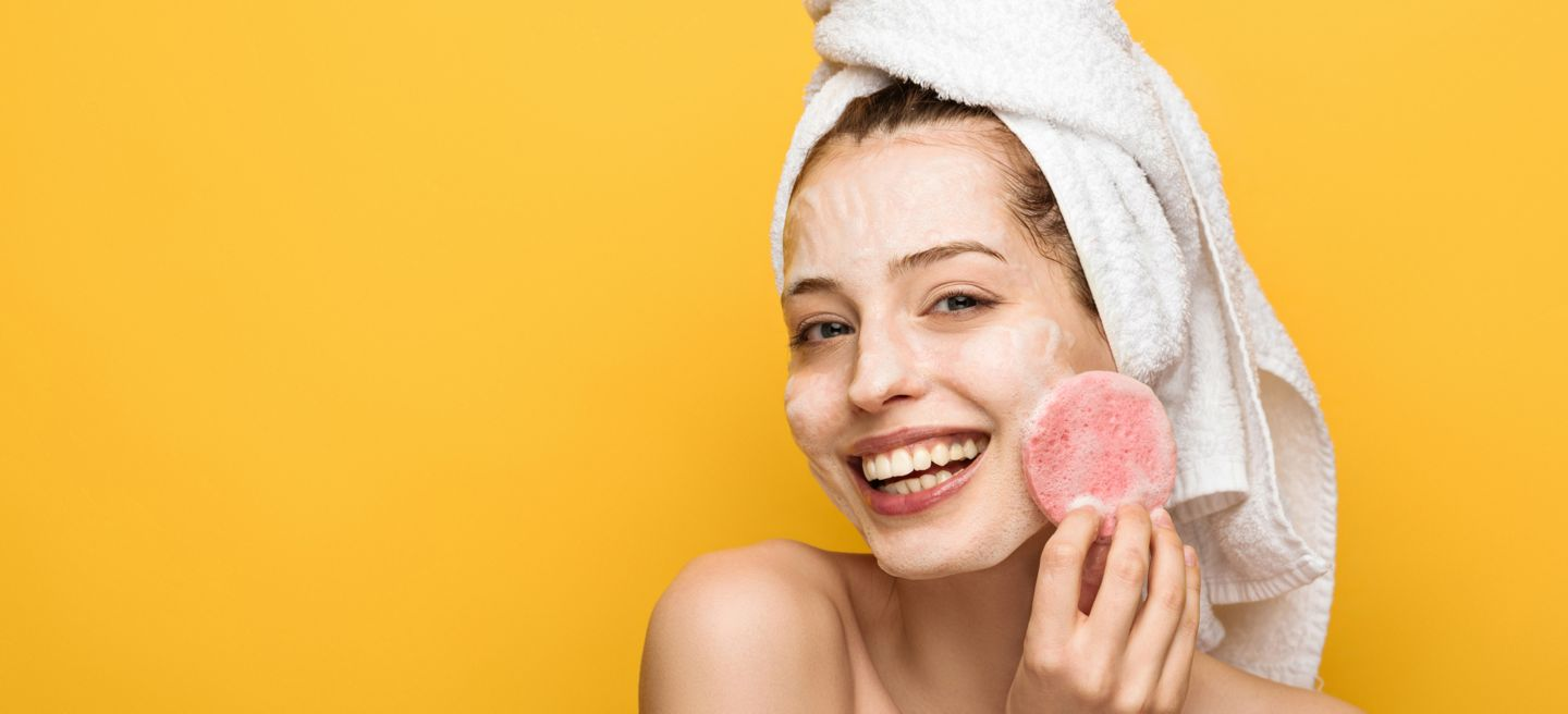 Woman in head towel with sponge on her face.