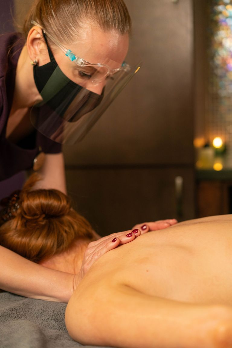 Spa therapist wearing PPE in Kohler Waters Spa while giving a massage