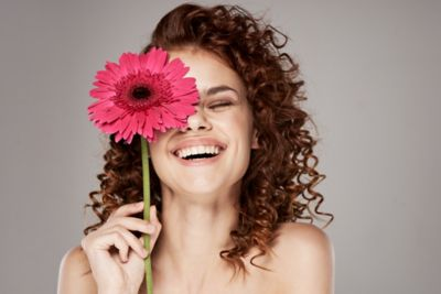 Woman in with pink flower over her face.