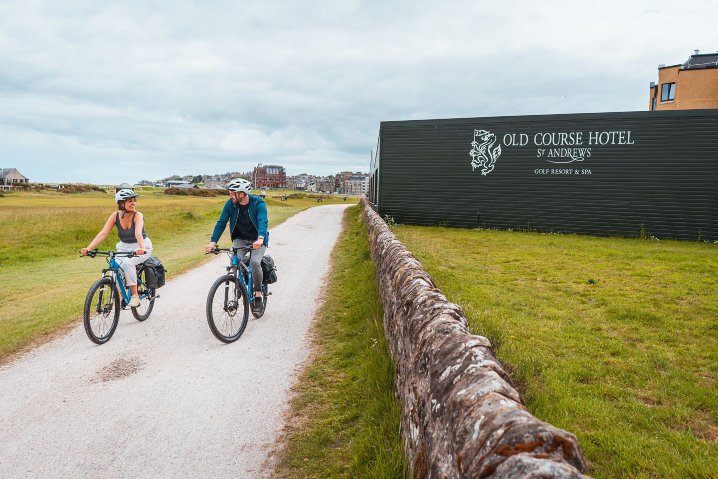 Man and woman cycling past the Green Sheds of the Old Course Hotel  in St Andrews