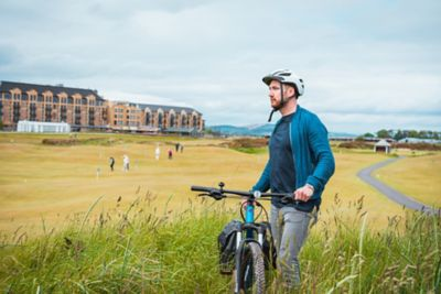 Man on bike outside the Old Course Hotel, Golf Resort & Spa in St Andrews