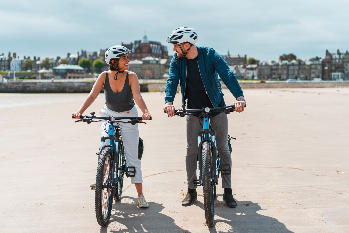 Man and woman cycling on West Sands Beach in St Andrews