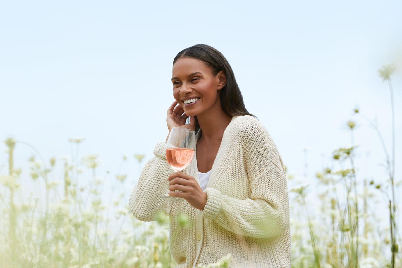 a woman drinking wine in a field