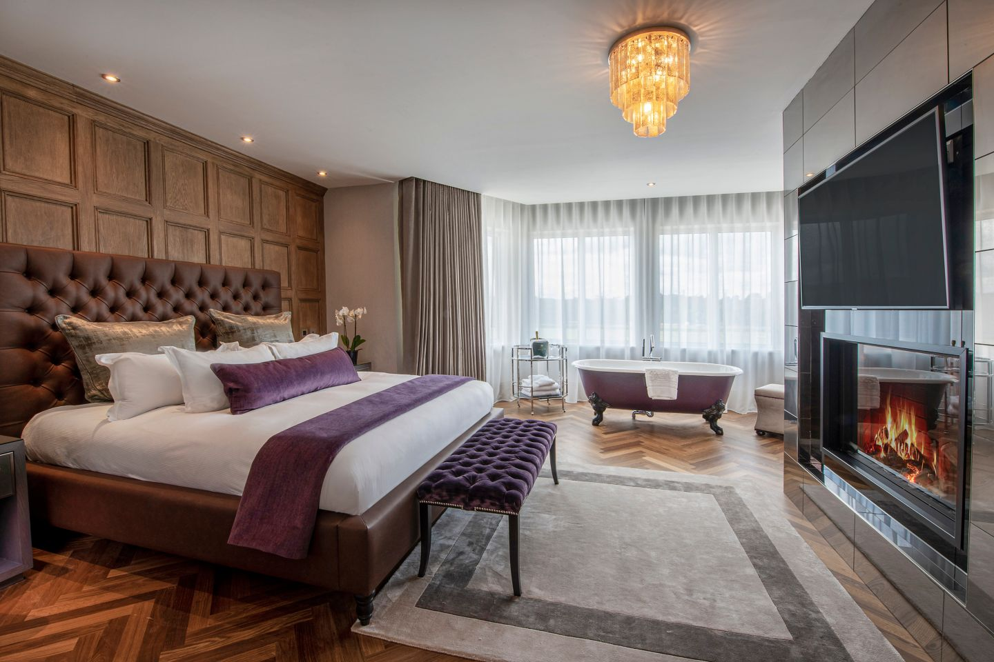 The Penthouse suite bedroom at the Old Course Hotel, St Andrews, with a fireplace and freestanding bath