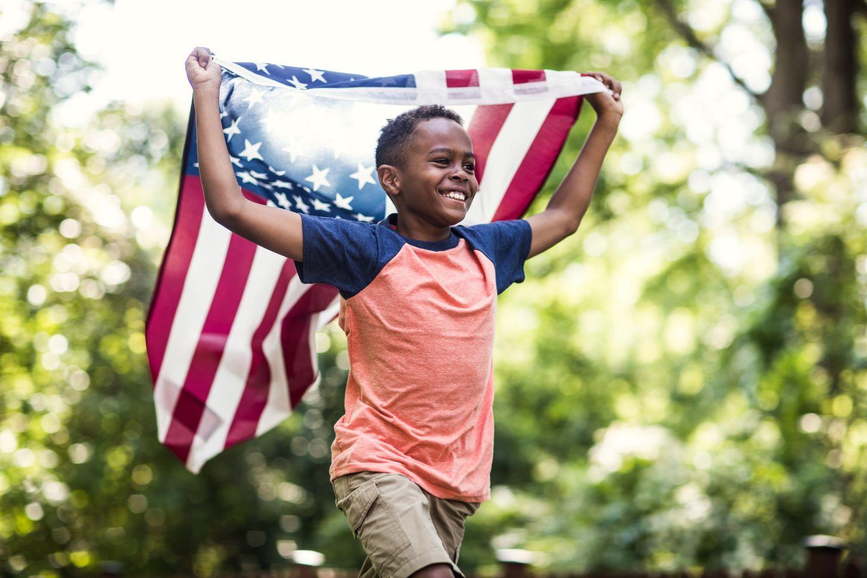 little boy running with an american flag
