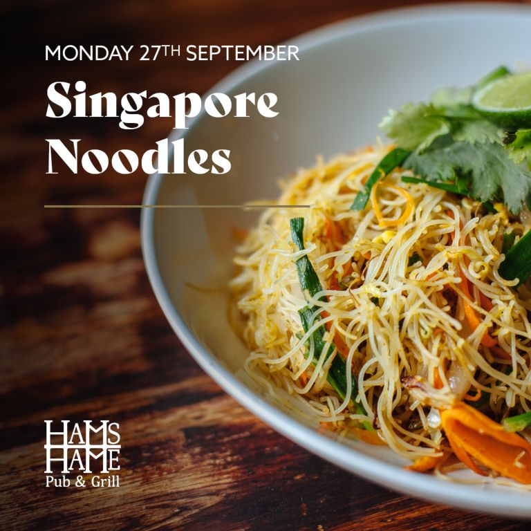 A dish of Singapore Noodles on a wooden table