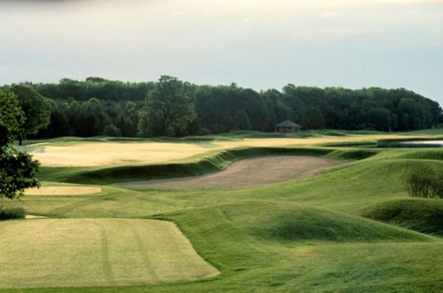Hole 9 of the Meadow Valleys course with golfers on the green in the distance and a water hazard in front.