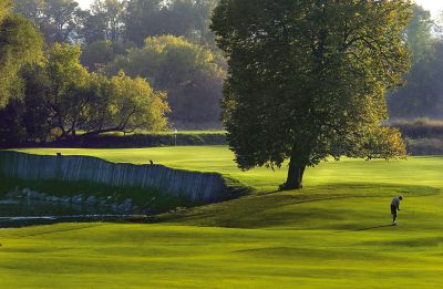 The green from the fairway of hole 16 on the River Course with a golfer on the right and bunker on the left.