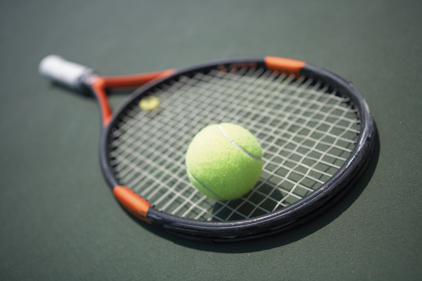 A tennis racquet and ball