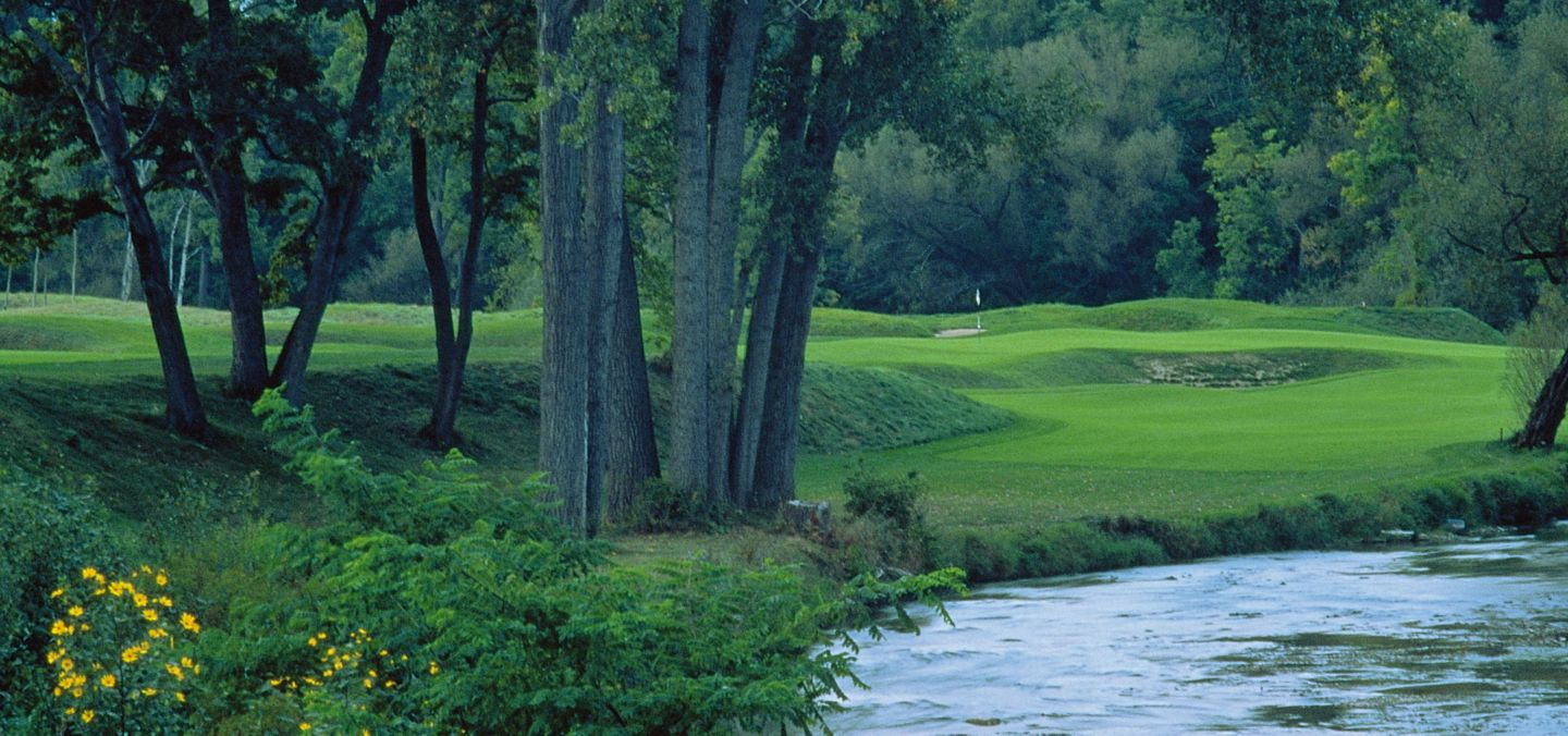 The green of hole 9 on the River Course is in the distance with the river on the right.