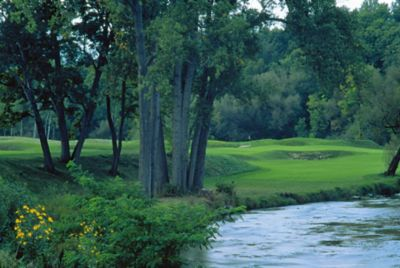 The green and flag stick of hole 9 on the River Course is in the distance with the river on the right.