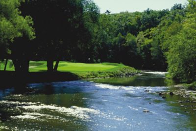 The green of hole 13 on The River course in the background with the river on the right.