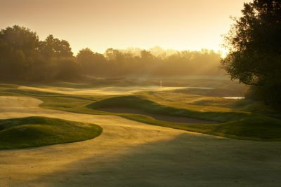 The green of hole 12 on The River course in the distance with sunlight and haze.