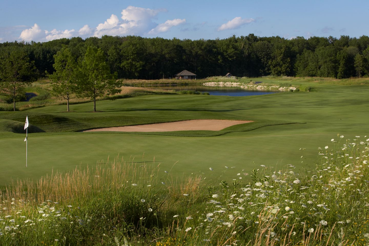 The first hole of the Meadow Valleys course from the back of the green with a view of the fairway and water hazard.
